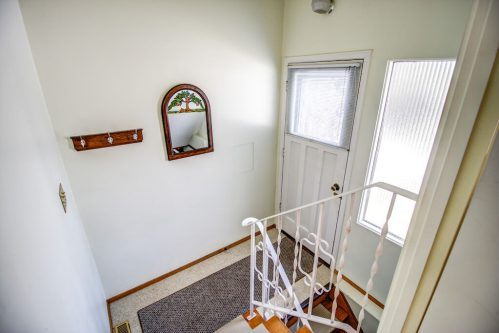 Interior entrance door with white metal railing in Calgary bungalow in Willow Park
