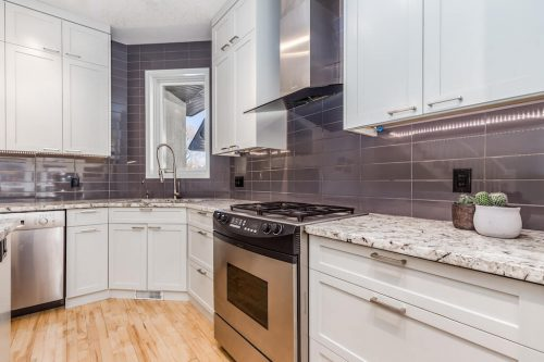 White-kitchen-cabinetry-stainless-steel-appliances-grey-tile-backsplash-granite-countertops-47-28-Avenue-SW-Erlton-Calgary-Home-For-Sale-Plintz-Real-Estate-House-realtor-realty