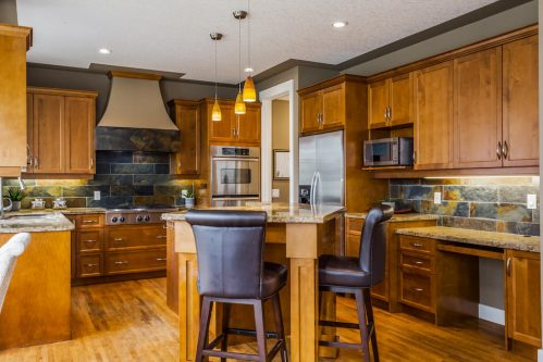 Luxury kitchen with island and leather stools in home for sale by Plintz Real Estate.