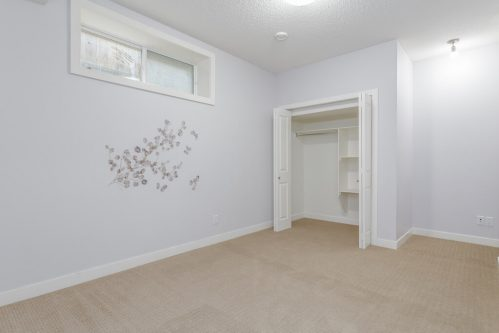 Basement bedroom with branch and leaves painted on wall.