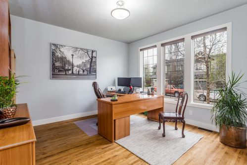 Den office with desk and large windows in home for sale in Calgary.
