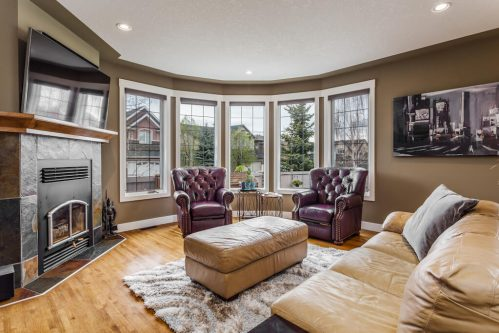 Living room with large bay windows and accent chairs in California Custom Home in Evergreen Calgary.
