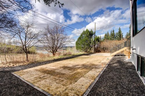 New sod and landscaping in backyard with view of Bow River at luxury Calgary homes.