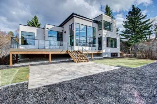 Backyard view of new modern home with large windows and glass railings at 2432 Sovereign Crescent SW in Calgary.