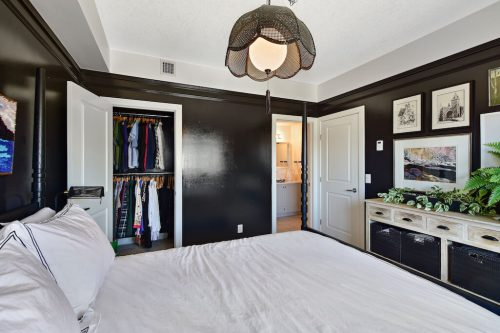 Bedroom with black walls and basket chandelier at 304 1108 15 Street SW Condo for sale in Sunalta Calgary