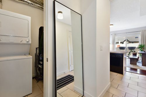 Entry hall with in-suite laundry with stacking washer and dryer at 304 1108 15 Street SW Condo for sale in Sunalta Calgary