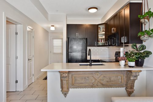 Condo kitchen with mocha cabinetry at 304 1108 15 Street SW Condo for sale in downtown Calgary