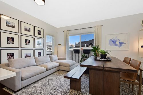 Furnished living dining room with black and white photo frames and grey chaise couch in Calgary condo