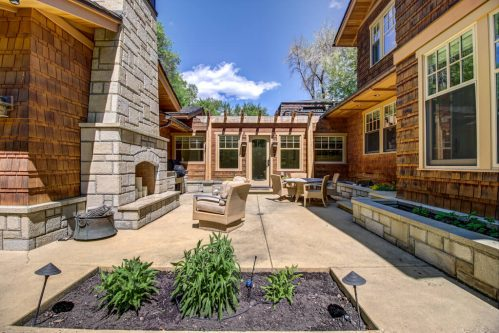 Backyard patio with outdoor fireplace and built-in barbecue in Rideau Park Calgary home.