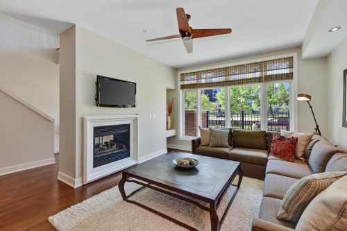 Living room with double sided fireplace ceiling fan and large windows Cityscape Executive Condo Eau Claire Calgary Plintz Real Estate For Sale