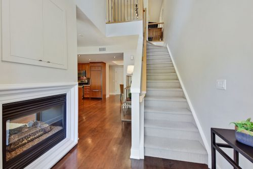 Fireplace and staircase Cityscape Executive Condo Eau Claire Calgary Plintz Real Estate For Sale