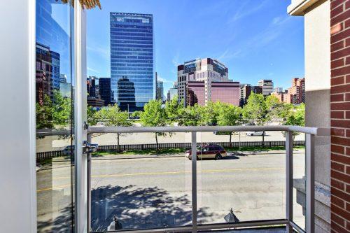 Balcony view of city skyscrapers Cityscape Executive Condo Eau Claire Calgary Plintz Real Estate For Sale