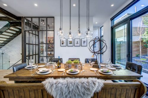 Ultra modern industrial rustic design dining room with wine cellar and pendent lights in Bridgeland Calgary Home.
