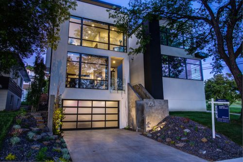 Three story luxury glass home in Bridgeland Calgary at night.