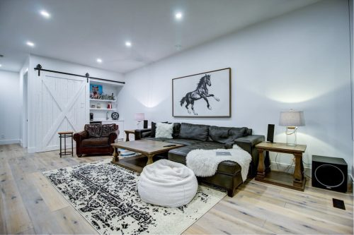 Media room on third story with wet bar and black and white horse art in Bridgeland luxury home.