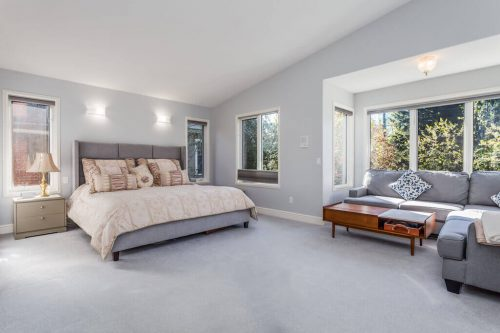 Large master bedroom with king bed, reading nook and vaulted ceilings at 619 Crescent Boulevard SW in Elboya, Calgary home for sale by Plintz Real Estate.