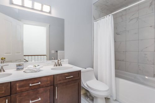 Bathroom with dual vanity and marble tile surround