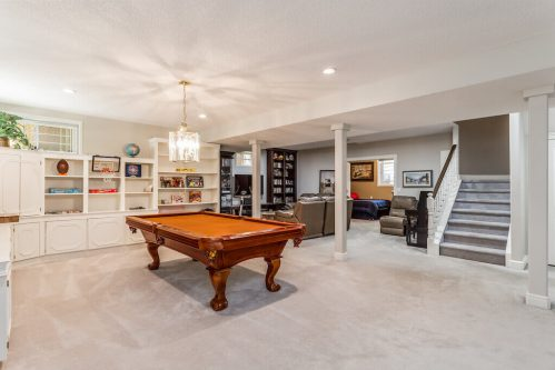 walkout basement with pool table and custom built-ins and media room at luxury Elboya home