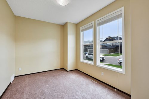 Den with morning sunshine through large windows