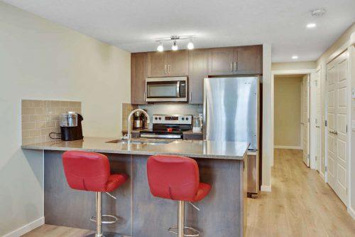 Kitchen breakfast bar in Zen Seton Calgary Condo for sale by Plintz Real Estate