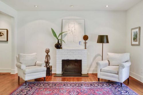 Two white accent chairs beside white brick fireplace at 2324 12 Street SW For Sale Pintz Real Estate.