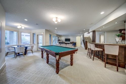 Walkout recreation room with pool table and wet bar.