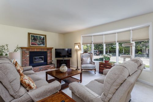 Living room with brick fireplace and bay window in Calgary home for sale.
