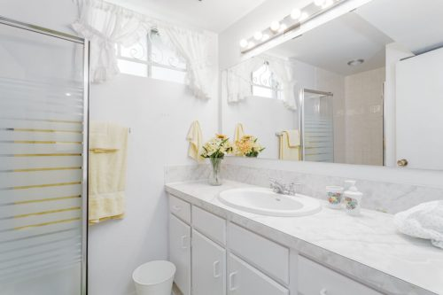 White bathroom in Calgary home for sale.