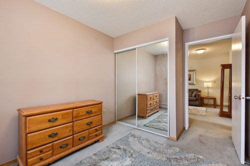 Bedroom with mirrored closet in condo for sale by Plintz Real Estate at 102, 2508 17 Street SW.