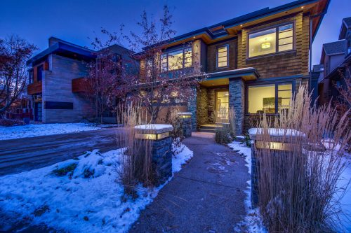 Front exterior at twilight of luxury home in Roxboro Calgary