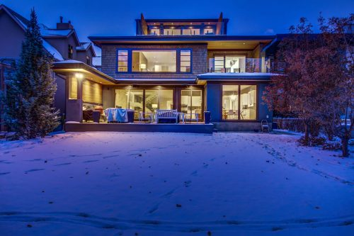 Twilight exterior of back of luxury home in Calgary for sale by plintz real estate