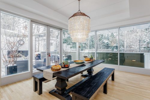 Dining room with floor-to-ceiling windows in luxury home for sale by Plintz Real Estate in Calgary Alberta.