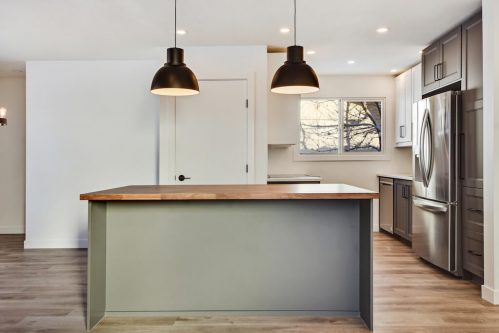Two-toned cabinetry in fully renovated kitchen at 1212 60 Street Se Calgary.