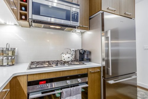 Countertop gas stove and stainless steel refrigerator in Tribeca condo building in Mission
