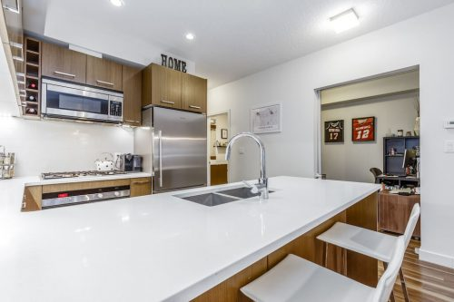 Modern kitchen with quartz countertops and walnut veneer cabinetry in condo for sale Calgary