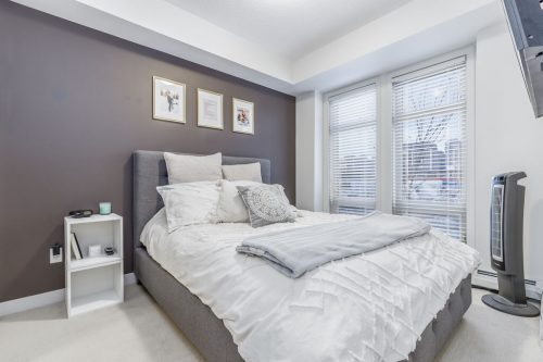 Master bedroom with grey feature wall at Tribeca Mission Calgary condo for sale Plintz Real Estate