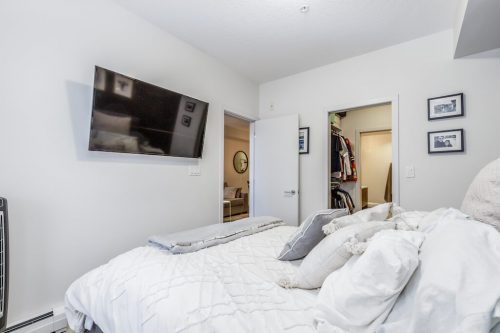 Master bedroom with wall mounted TV at #216, 323 30 Ave SW Calgary condo