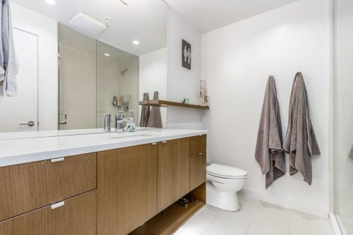 Ensuite bath with walnut vanity and quartz counters in Calgary condo for sale by Plintz Real Estate