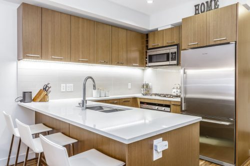 Modern condo kitchen with walnut cabinets and stainless steel appliances in Calgary condo for sale by Plintz Real Estate