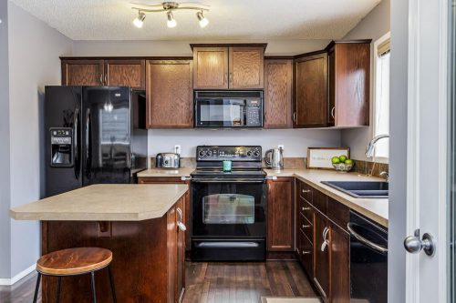 Kitchen with dark wood cabinetry and island in detached Evergreen home for sale by Plintz Real Estate.