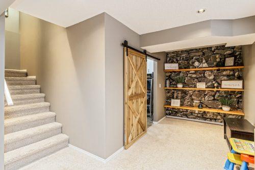Laundry room with barn door at 287 Everglen Way SW Calgary.