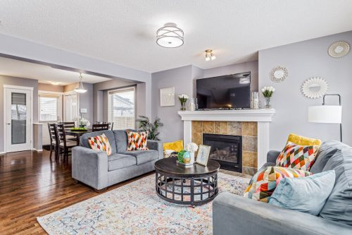 Living room with tile and mantel fireplace at 287 Everglen Way SW in Calgary Alberta for sale by Plintz Real Estate