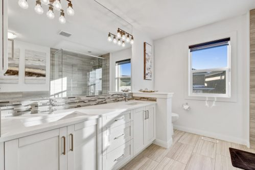 Double white vanity with mosaic tile backsplash in Evanston Calgary home for sale by Realtor Dennis Plintz
