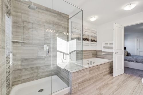 Luxury ensuite bath with grey brown tiles and oversized glass shower in Evanston Calgary home for sale by Plintz Real Estate