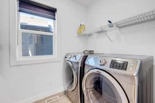 Stainless steel washer and dryer with storage.