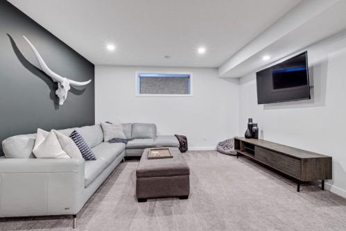 Basement media room with white and grey walls in Calgary home for sale.