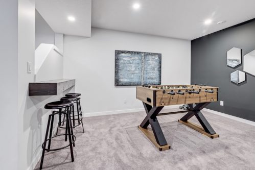 Basement rec room with foosball table and bar in Evanston Calgary home