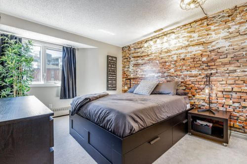 Brick accent wall in condo master bedroom in Calgary inner city for sale by Plintz Real Estate