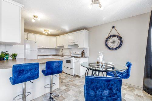 Royal blue stools in white kitchen of Bridgeland Calgary condo