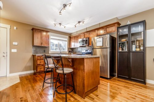 Kitchen island with breakfast bar at 193 Rainbow Falls Manor in Chestermere